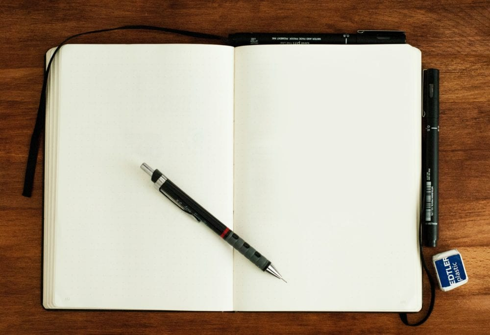 open journal with blank pages and pen